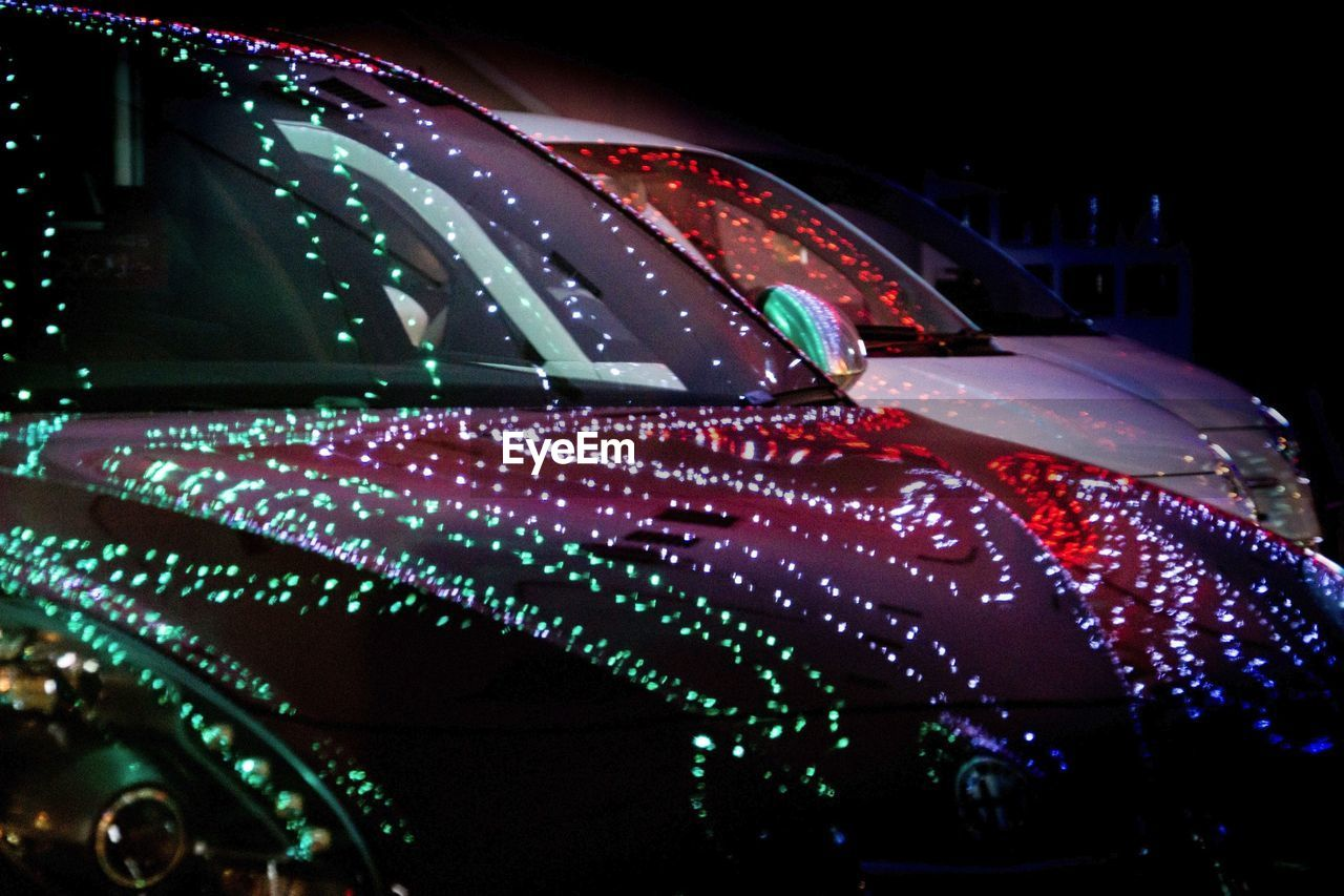 Reflection of illuminated string lights on car at night