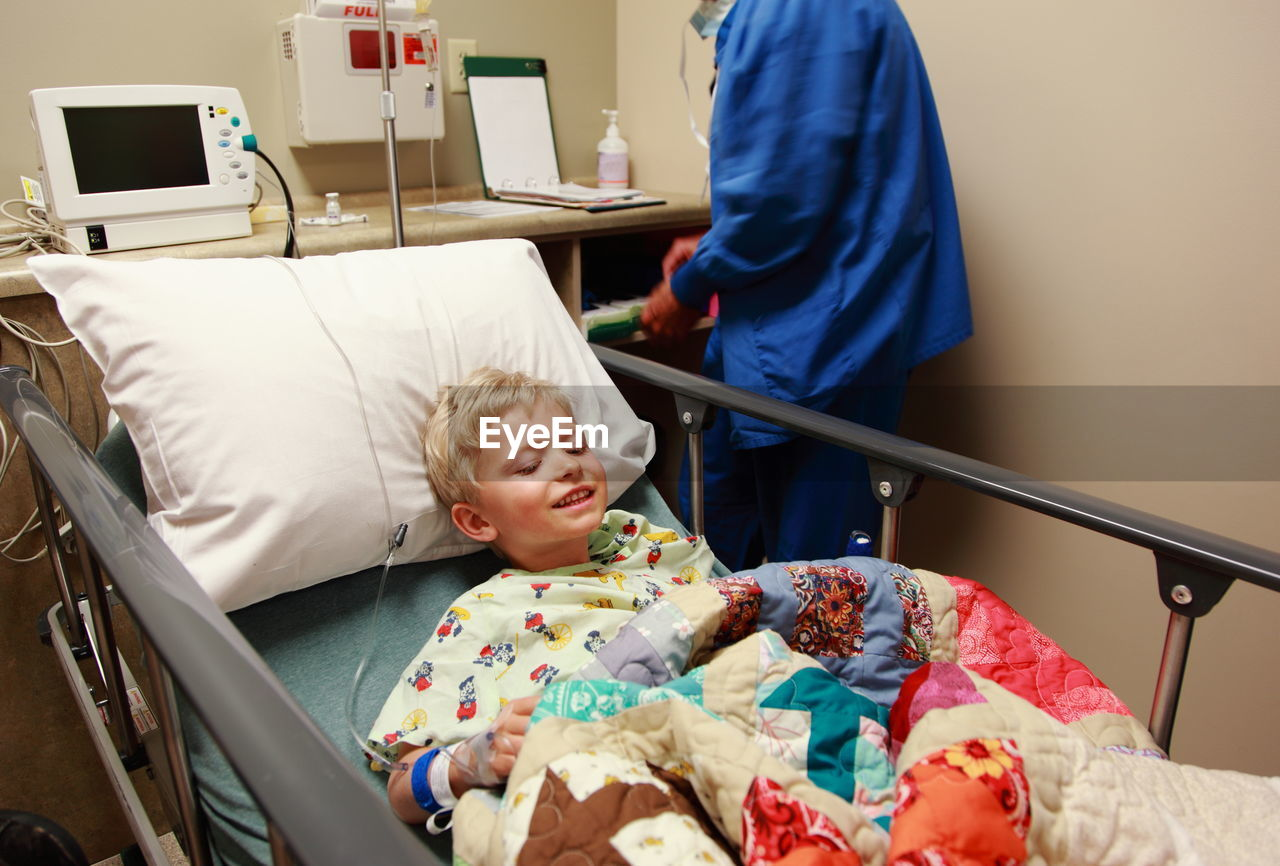 Midsection Of Doctor Examining Boy Lying On Bed