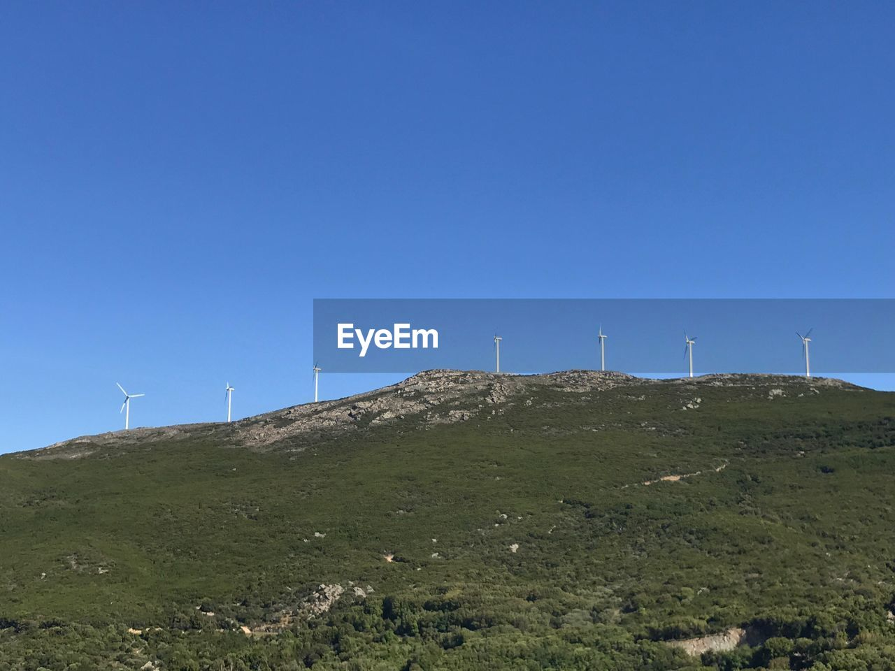 Low angle view of windmill on mountain against clear blue sky