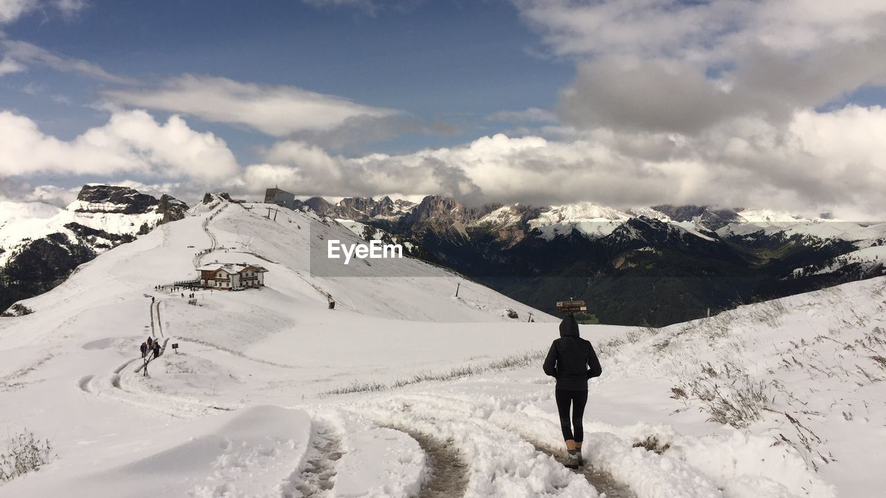 snow, winter, cold temperature, mountain, cloud - sky, sky, scenics - nature, beauty in nature, real people, one person, leisure activity, full length, lifestyles, covering, standing, white color, day, nature, snowcapped mountain, mountain range, outdoors, warm clothing