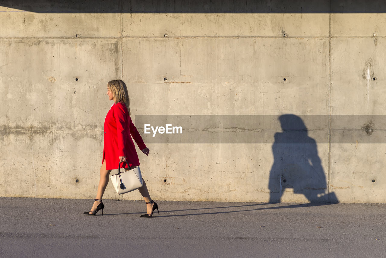Side View Of Woman Walking On Footpath Against Wall