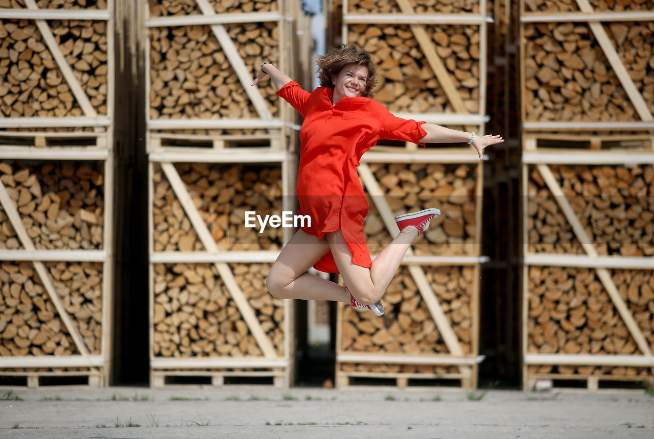 MIDSECTION OF WOMAN WITH RED UMBRELLA ON WOOD