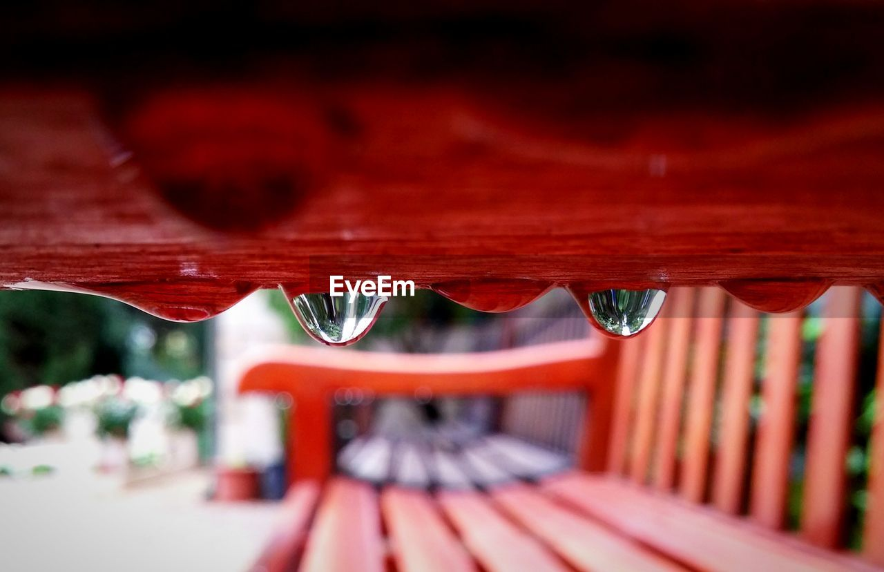 red, selective focus, close-up, focus on foreground, wood - material, day, no people, outdoors, nature, water, drop, metal, reflection, detail, pattern, design, architecture, surface level