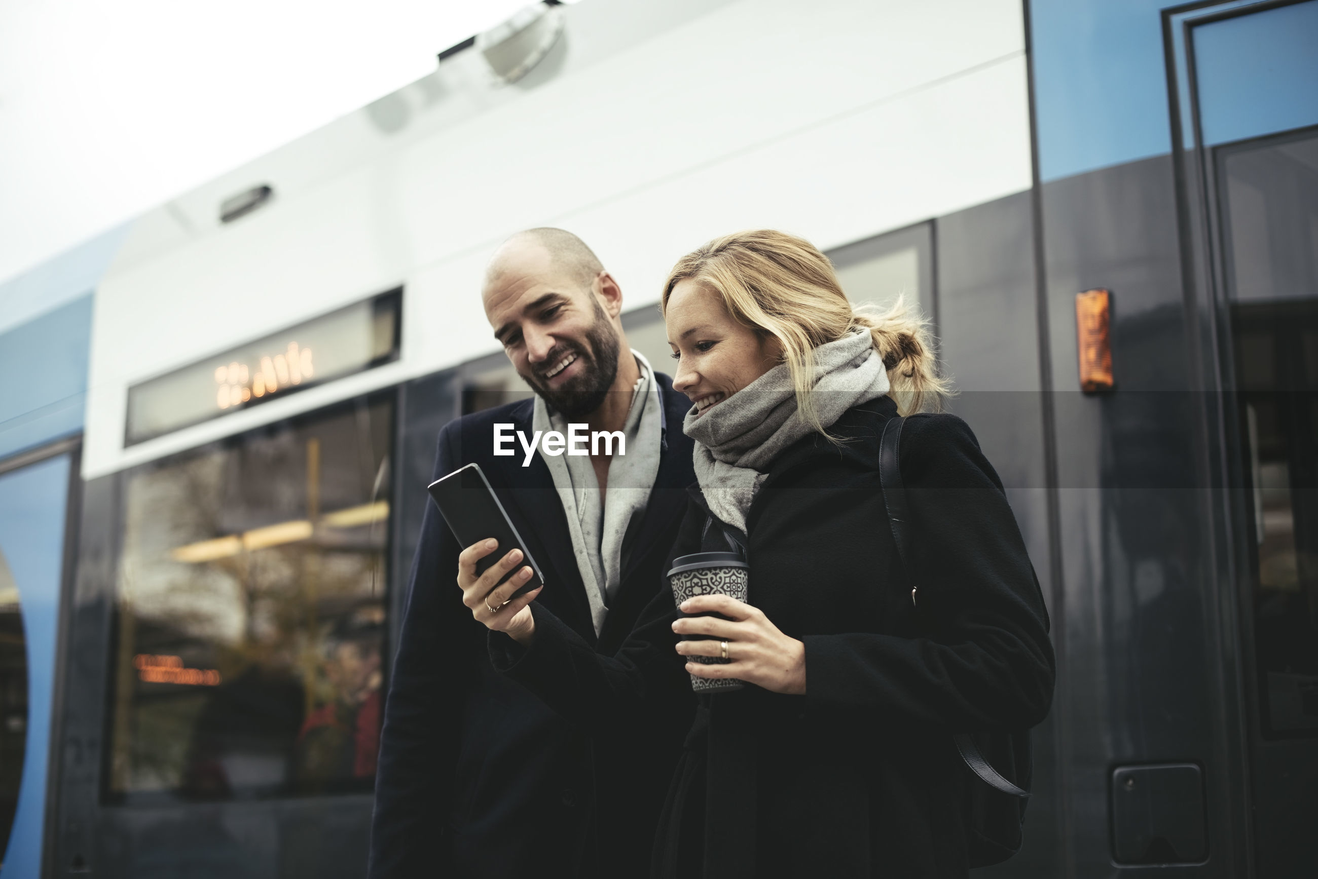 Smiling business people using mobile phone while standing against tram