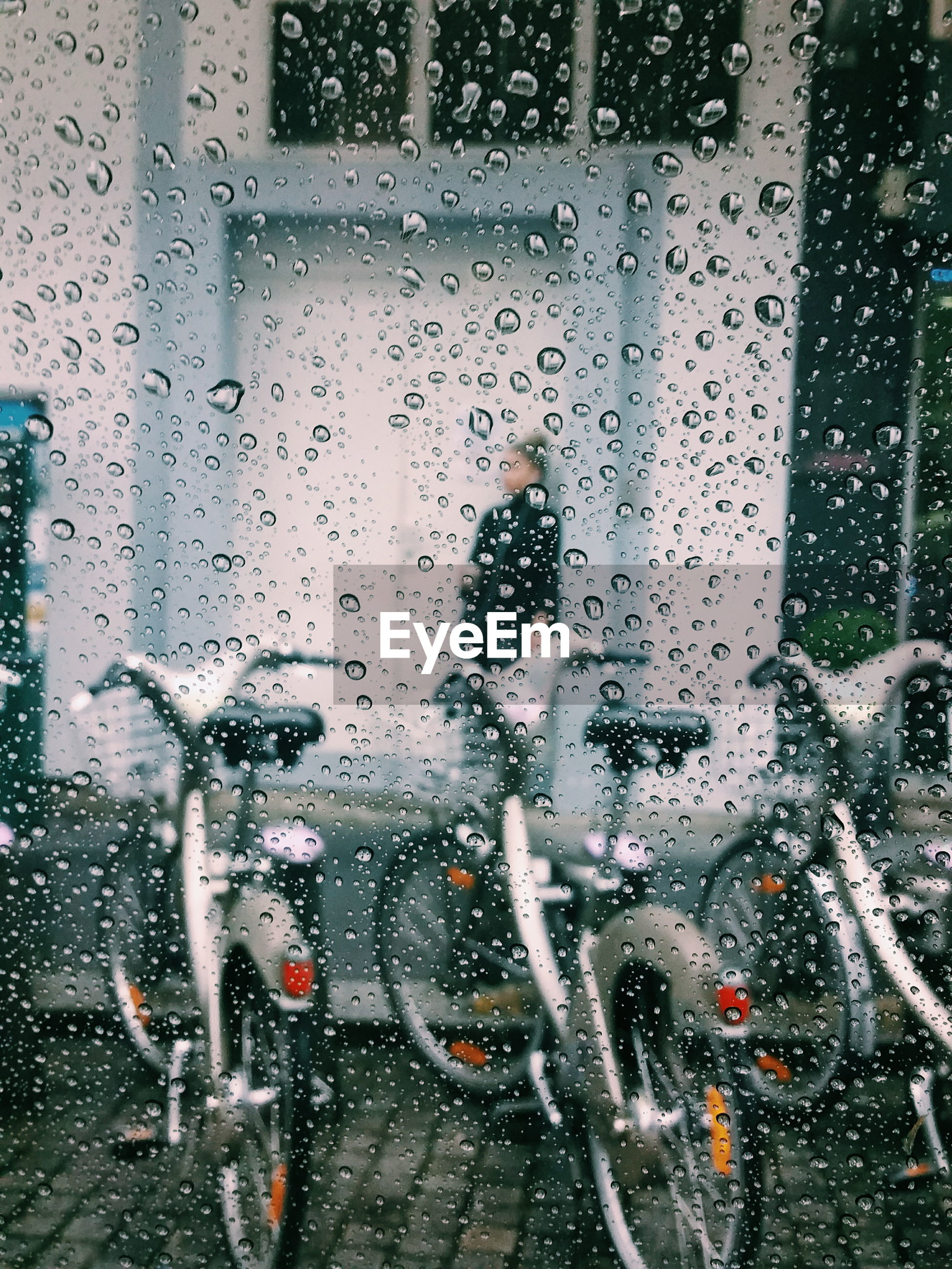 Water on glass with bicycle in background
