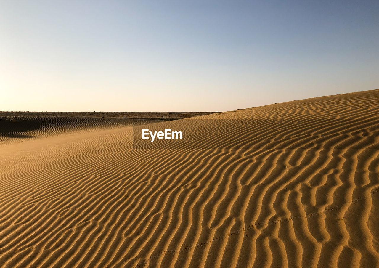 sand, land, scenics - nature, desert, landscape, sand dune, tranquility, climate, sky, environment, arid climate, tranquil scene, beauty in nature, clear sky, nature, no people, non-urban scene, horizon over land, horizon, day, outdoors