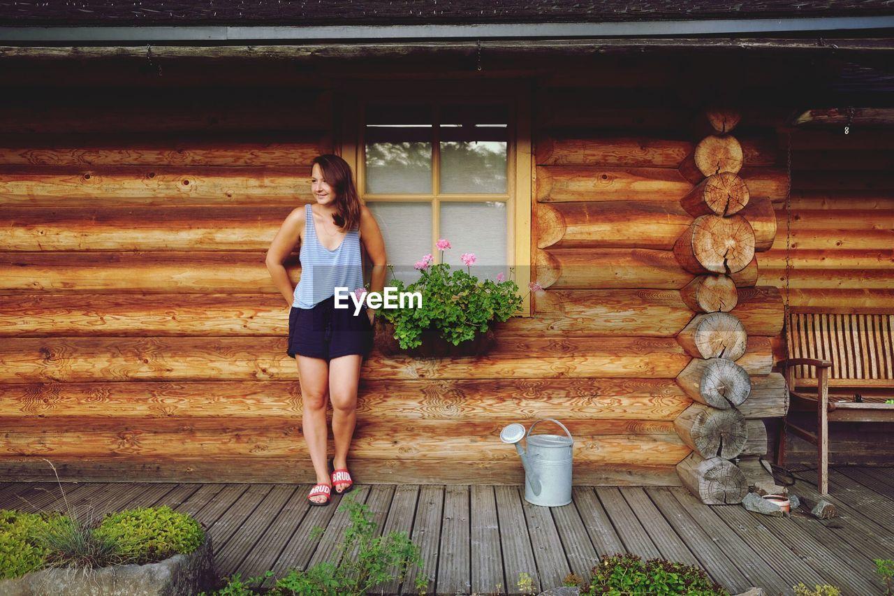 Full length of woman standing against log cabin