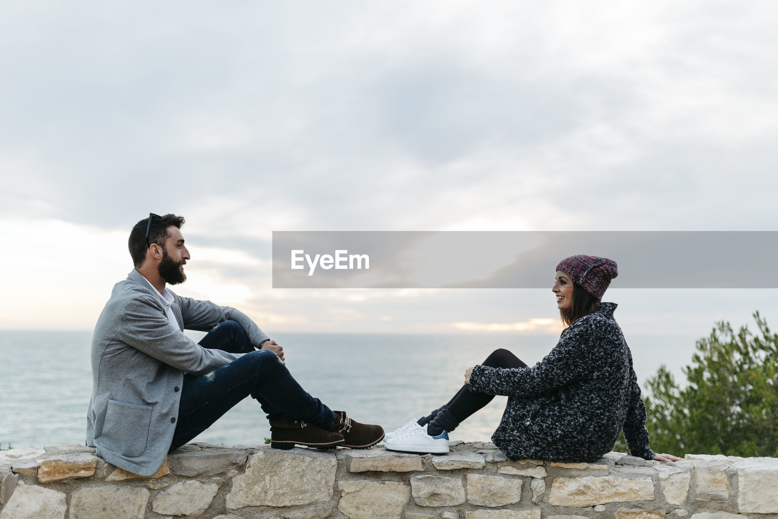 Side view full length of couple sitting on retaining wall by sea
