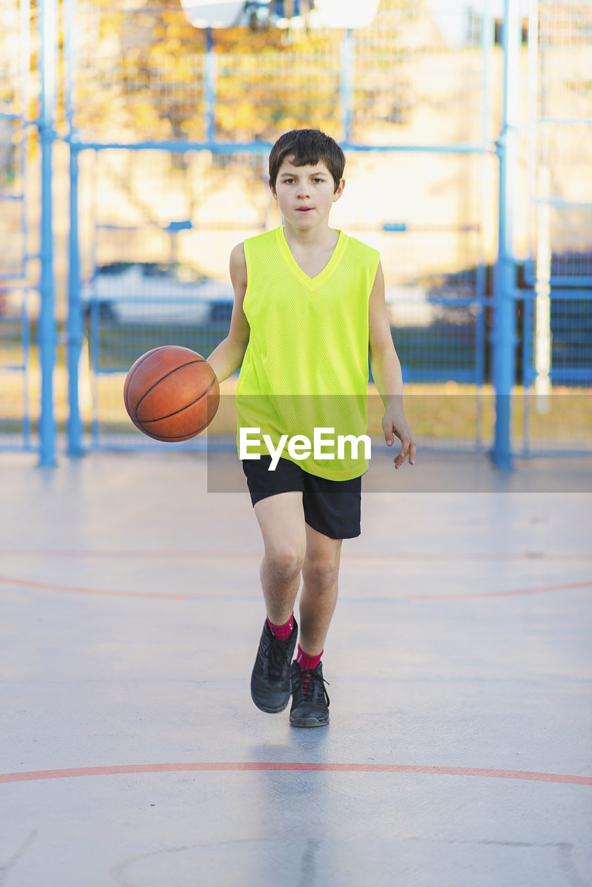 Portrait Of Boy Playing With Ball At Court