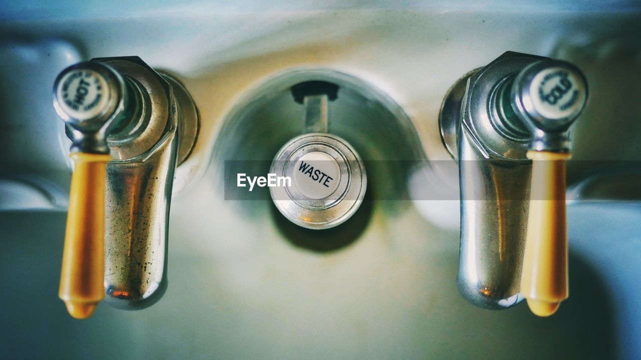 Directly Above View Of Taps With Text On Sink