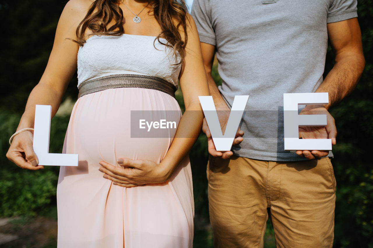 Midsection Of Man With Pregnant Woman Holding Love Text