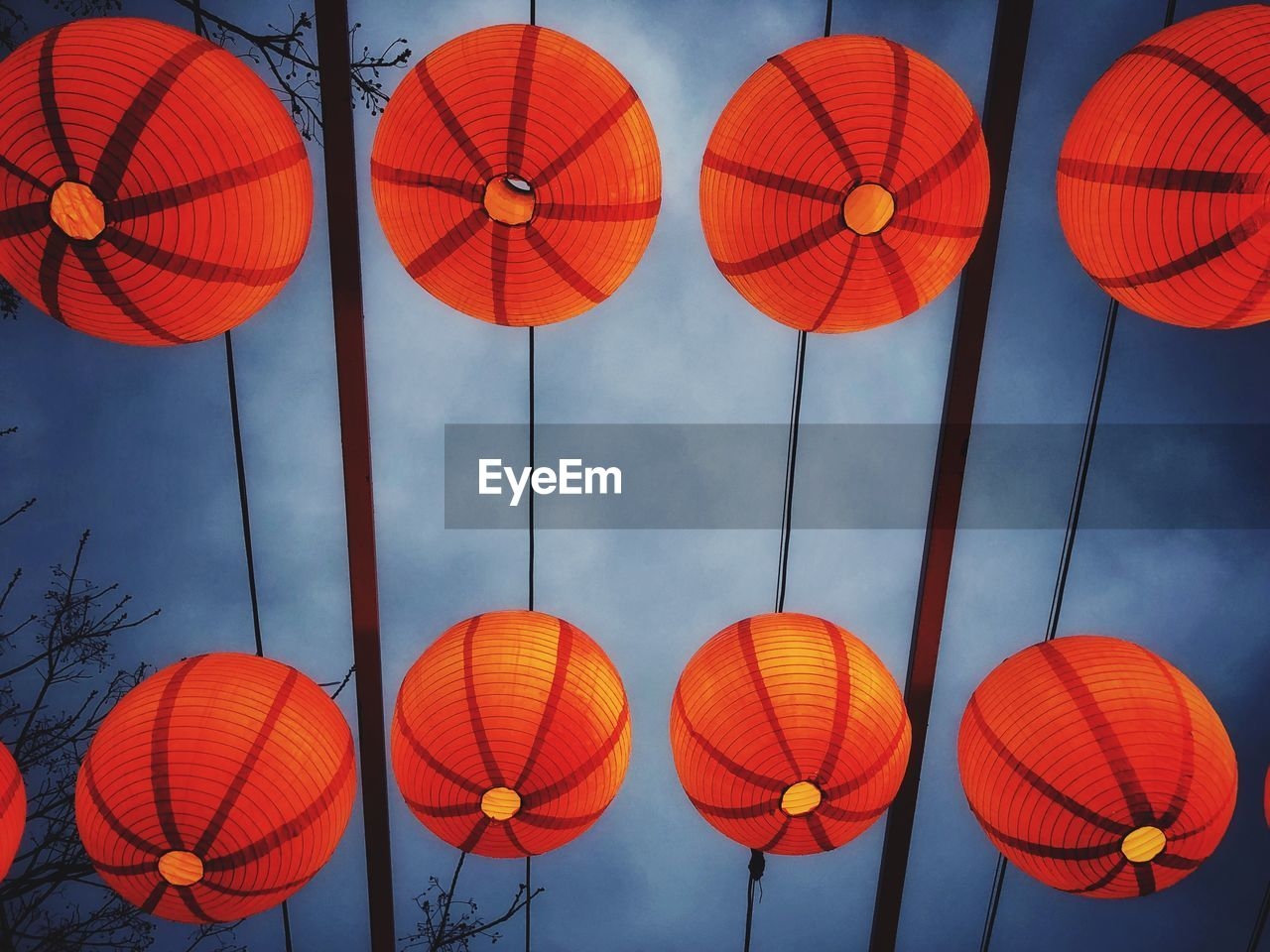 Low angle view of illuminated lanterns hanging against cloudy sky