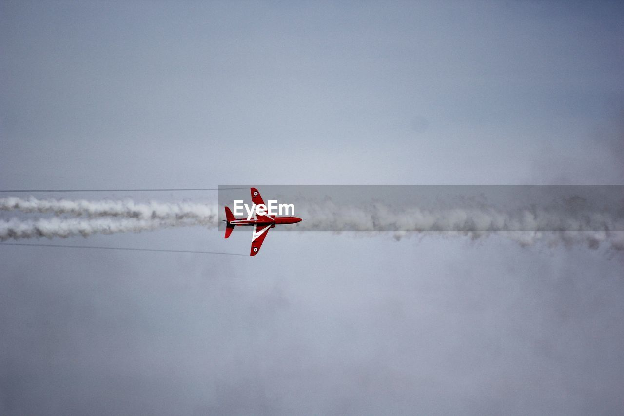 A single red arrow creating vapor trails