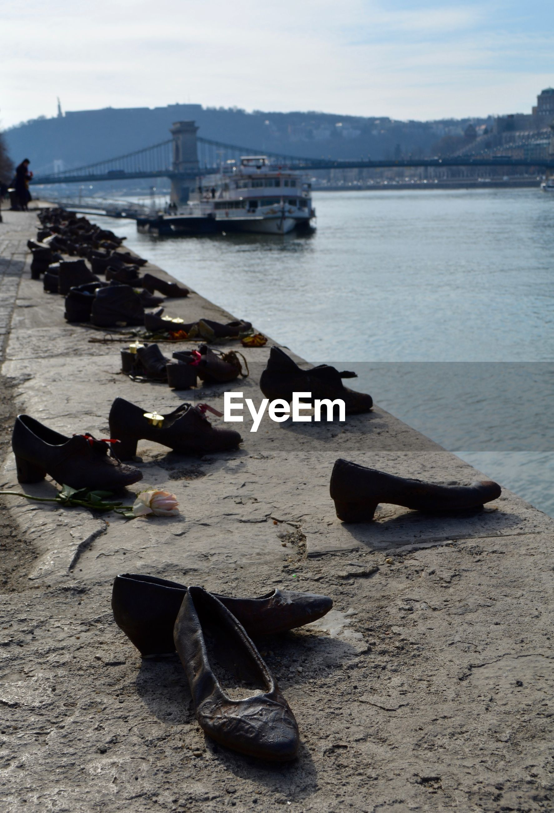 Shoes over river against sky in city