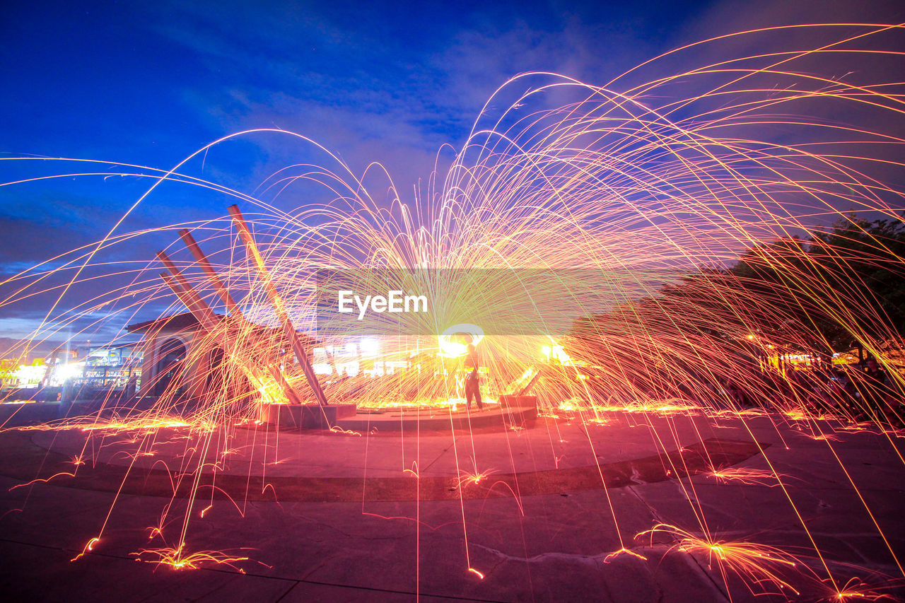 night, glowing, long exposure, motion, burning, celebration, heat - temperature, flame, wire wool, illuminated, firework display, firework - man made object, sky, outdoors, men, real people, full length, one person, firework, nature, people
