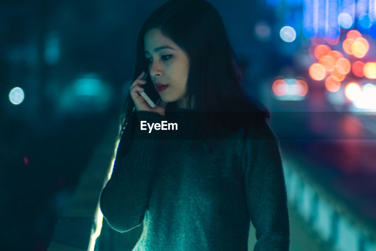 Young woman talking on phone at night