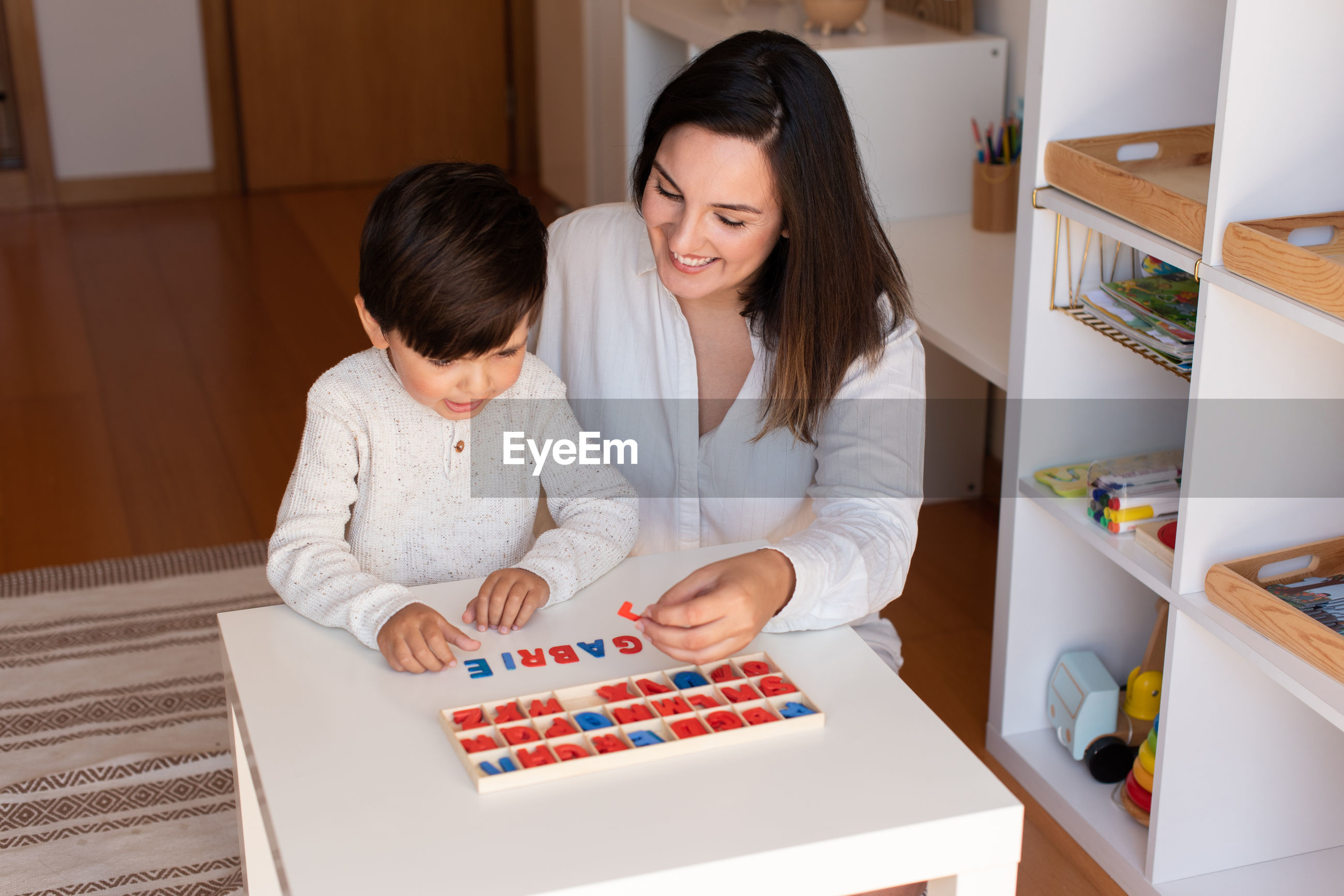 Mother assisting son in puzzle sitting at home