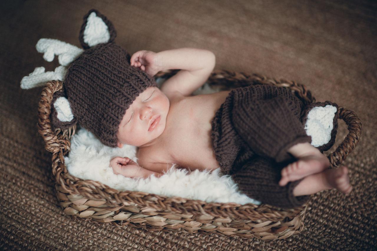 Cute baby boy sleeping in basket