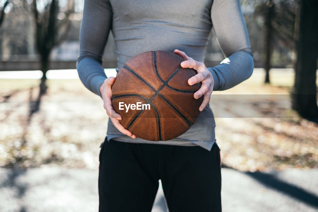 Midsection Of Man Playing Holding Basketball