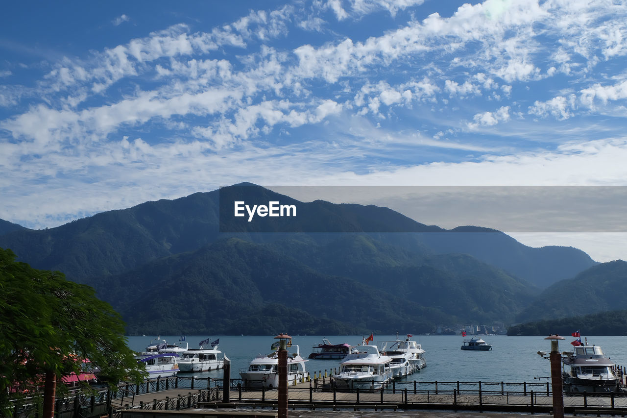 SCENIC VIEW OF BAY AGAINST MOUNTAINS