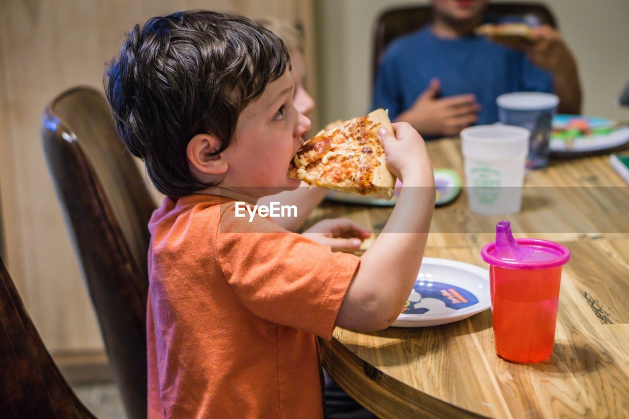 Side view of boy with siblings eating pizza at table