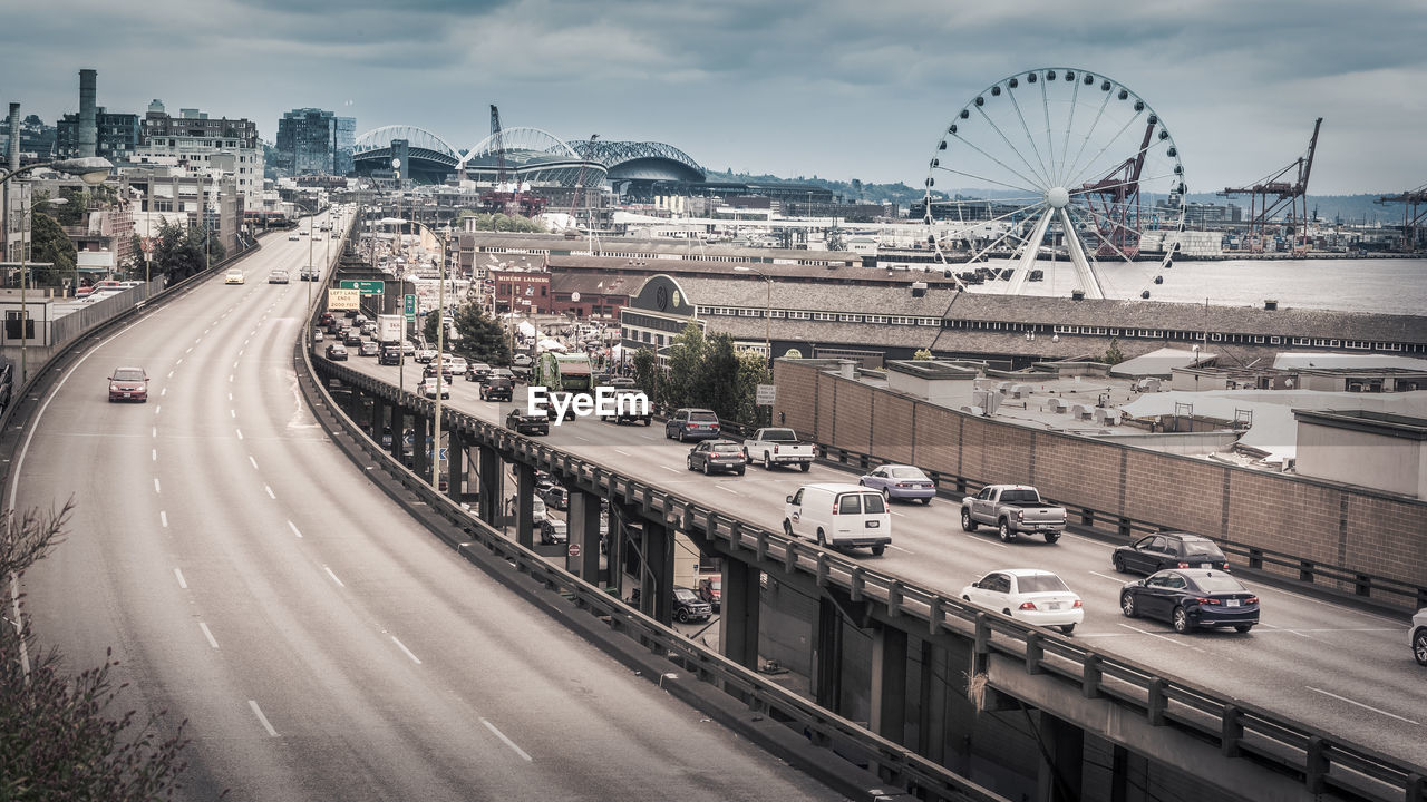 transportation, city, architecture, built structure, building exterior, road, high angle view, bridge, connection, street, bridge - man made structure, mode of transportation, land vehicle, sky, nature, motor vehicle, highway, car, traffic, no people, cityscape, multiple lane highway, outdoors