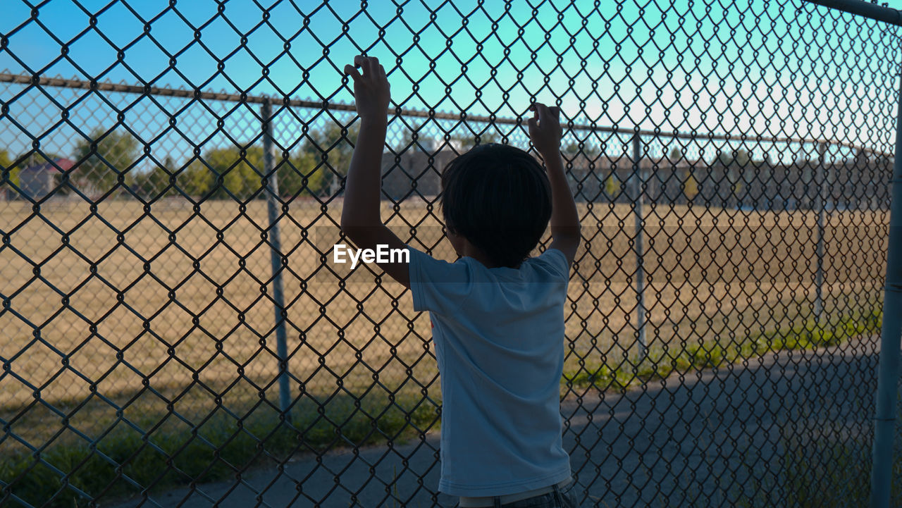 Rear View Of Boy Looking At Field While Standing By Chainlink Fence
