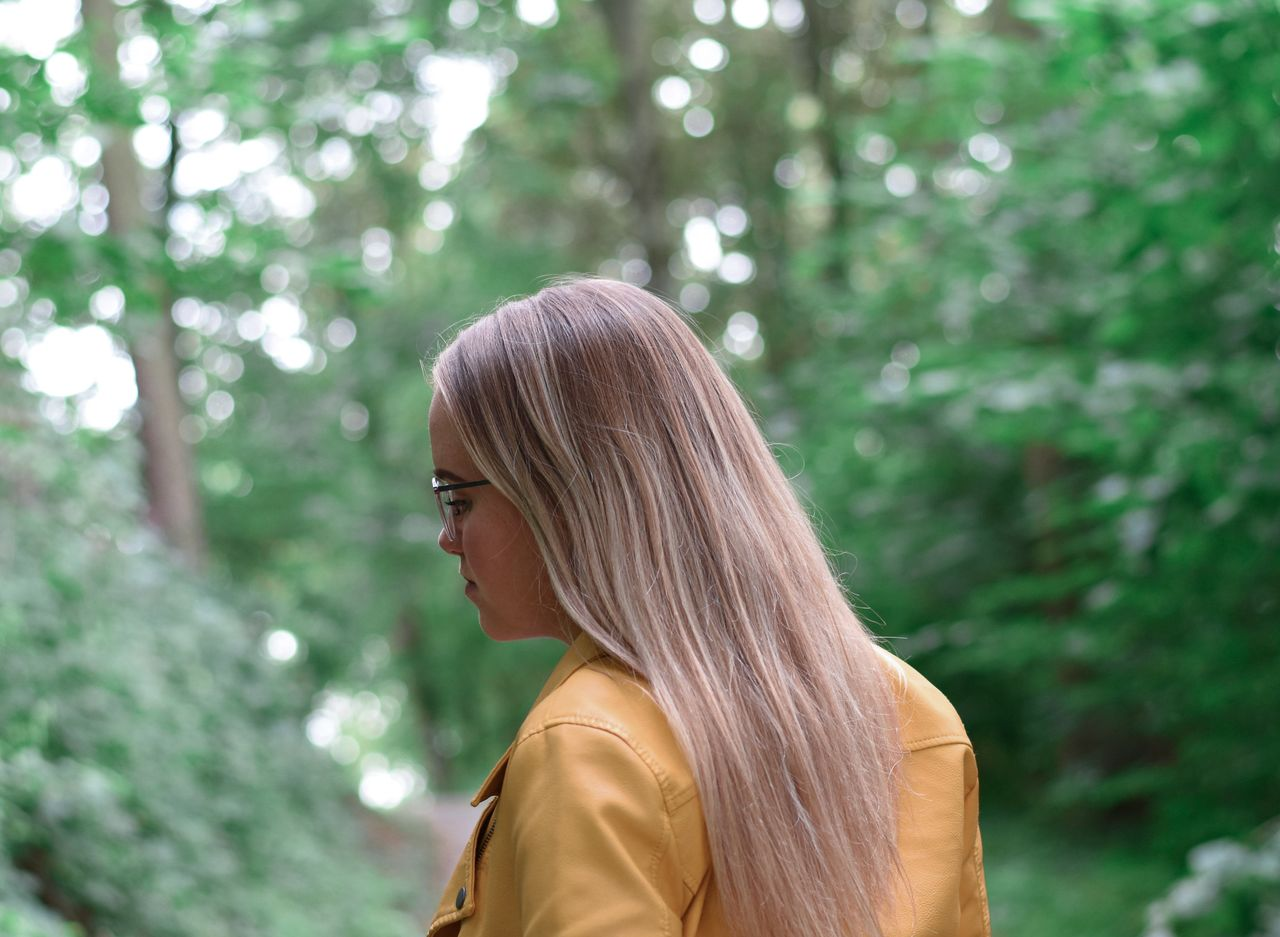 Side view of woman with blond hair standing in forest