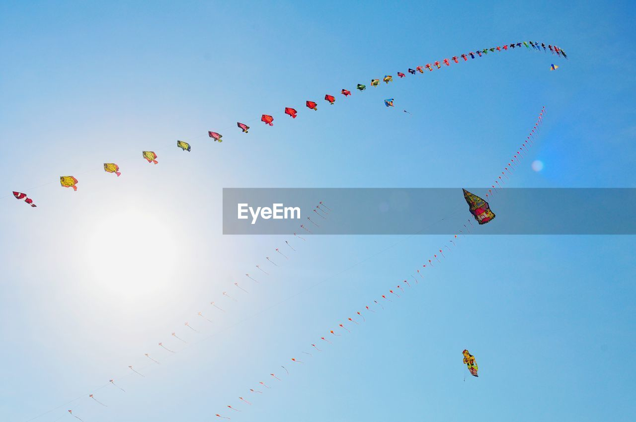 sky, low angle view, decoration, nature, celebration, blue, no people, day, sunlight, multi colored, flying, clear sky, outdoors, hanging, bunting, beauty in nature, kite - toy, string, lighting equipment