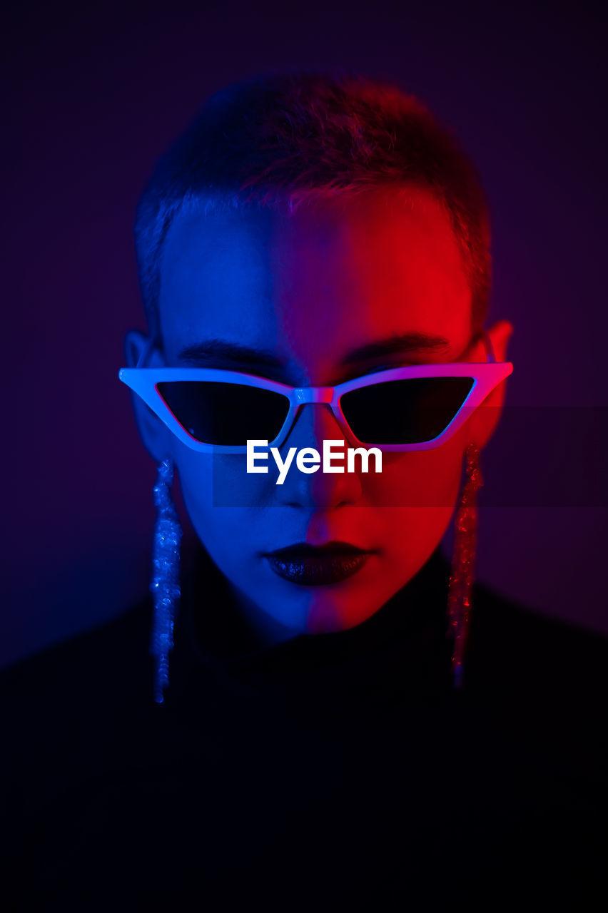 Portrait of woman wearing sunglasses against black background