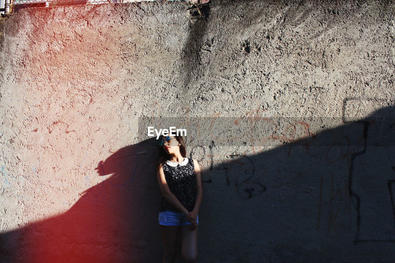 Young Woman Standing Against Wall On Sunny Day