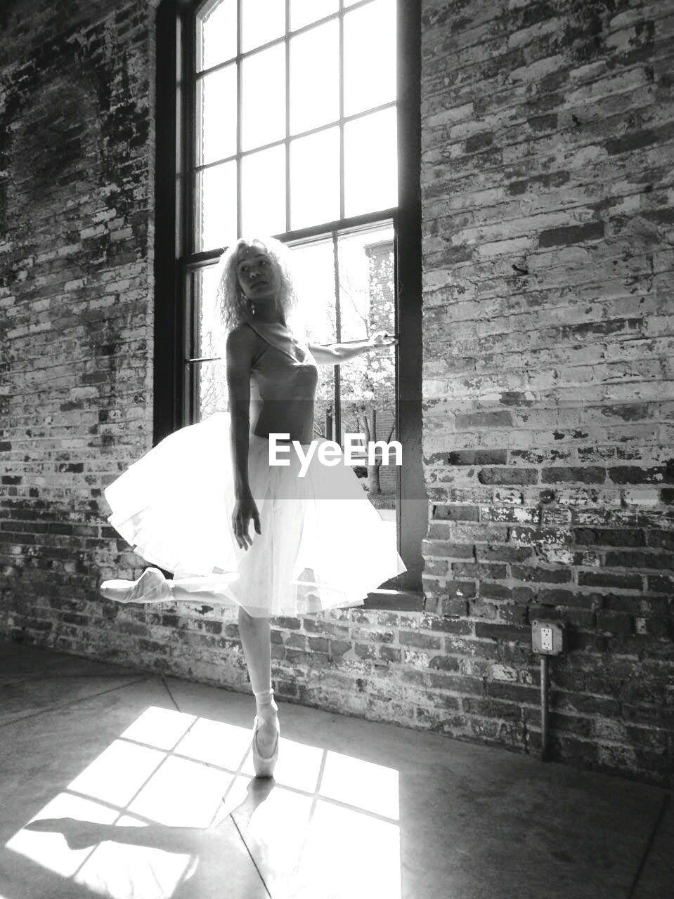 Ballet Dancer Practicing By Window At Dance Studio