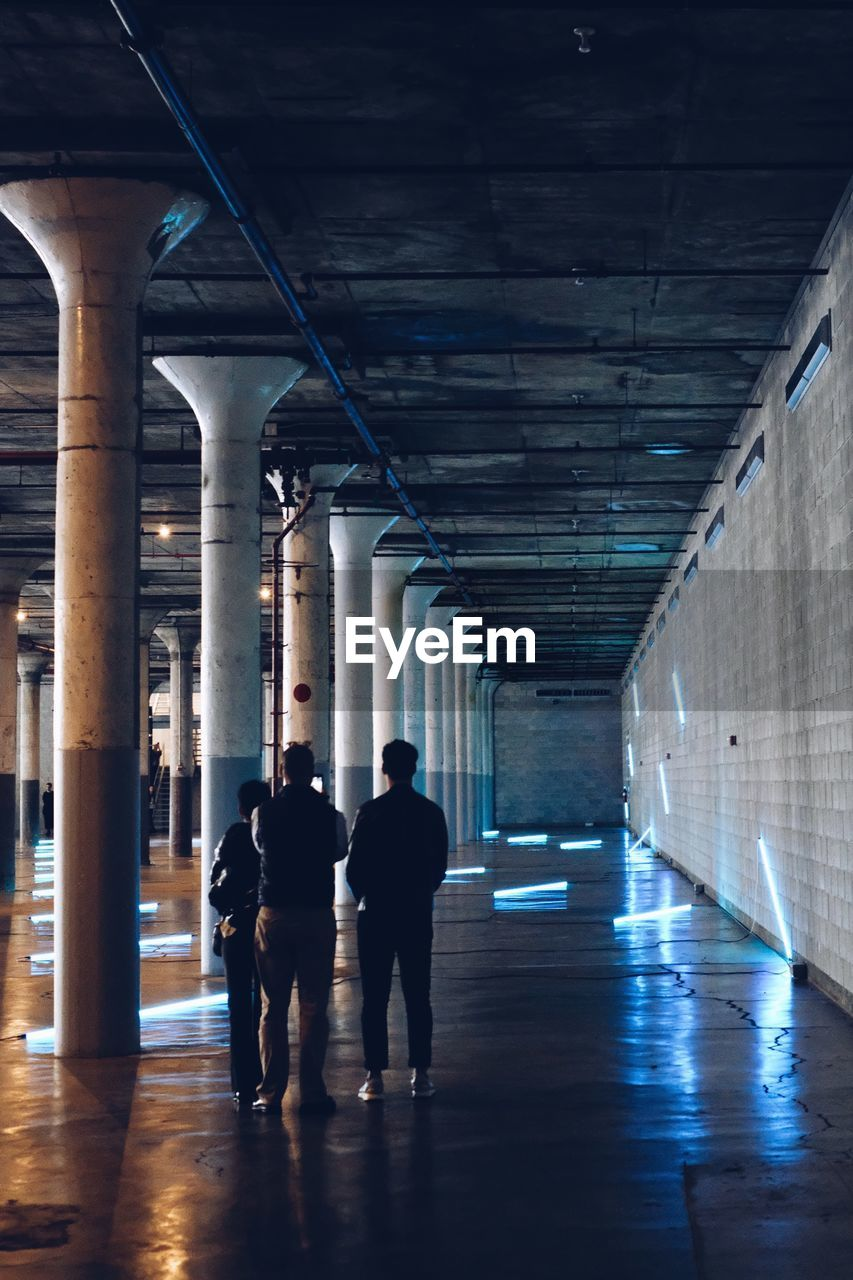 full length, indoors, architecture, walking, men, real people, rear view, built structure, the way forward, two people, illuminated, people, direction, lifestyles, arcade, women, corridor, leisure activity, flooring, building, ceiling, architectural column, underpass