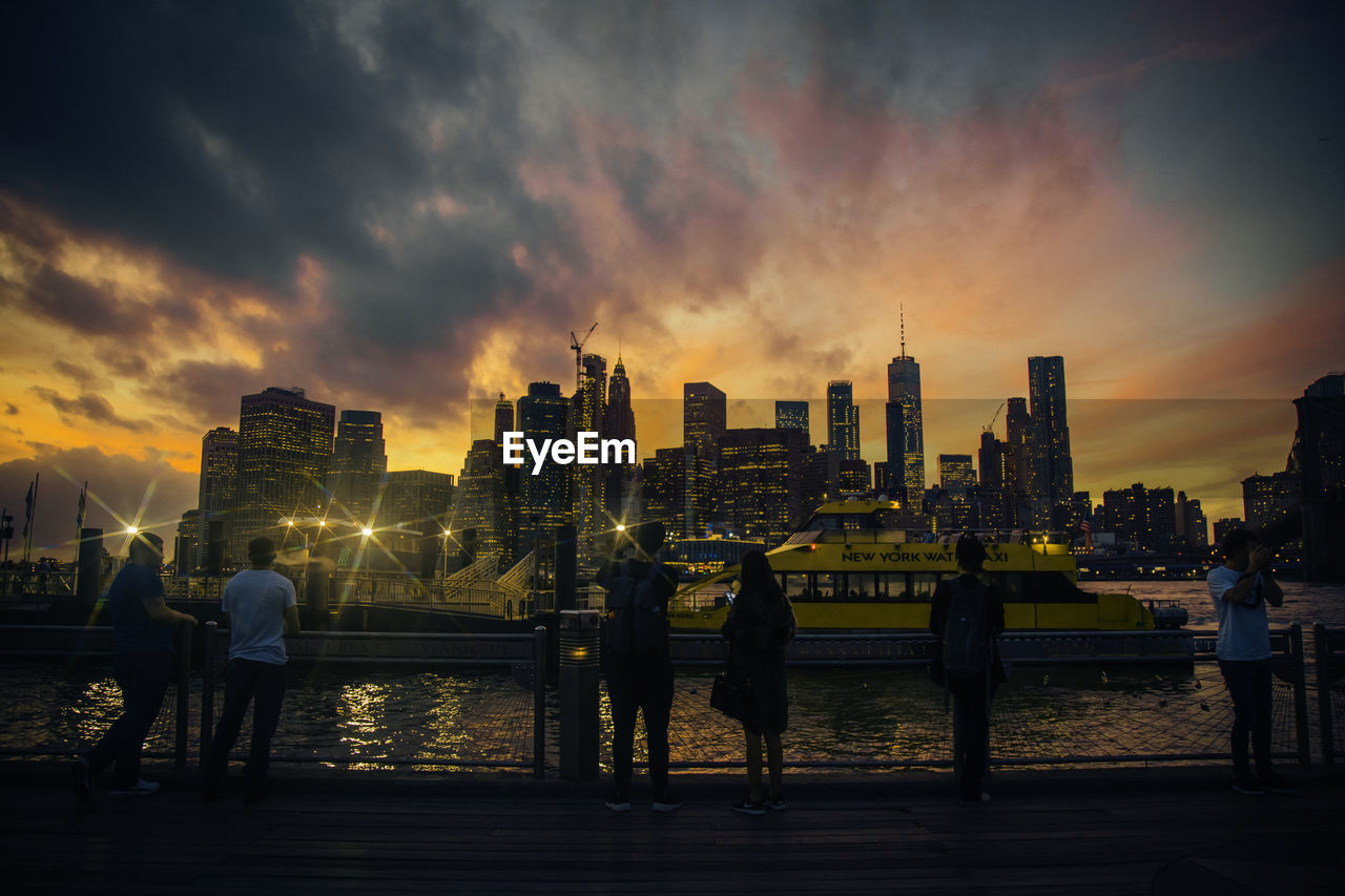 sky, architecture, building exterior, built structure, city, water, sunset, cloud - sky, nature, real people, cityscape, building, office building exterior, men, skyscraper, lifestyles, urban skyline, standing, railing, outdoors, financial district