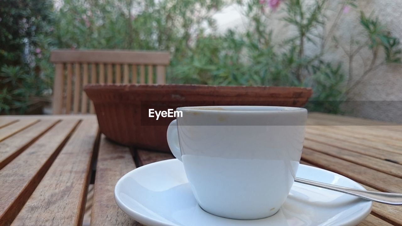 table, cup, wood - material, food and drink, mug, no people, focus on foreground, coffee cup, drink, seat, close-up, refreshment, day, still life, coffee, coffee - drink, saucer, empty, nature, outdoors, crockery, tea cup
