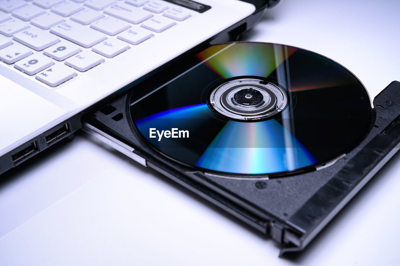 technology, computer, computer equipment, wireless technology, keyboard, laptop, computer keyboard, communication, connection, close-up, indoors, no people, compact disc, still life, portable information device, blue, data, high angle view, equipment, computer part, silver colored