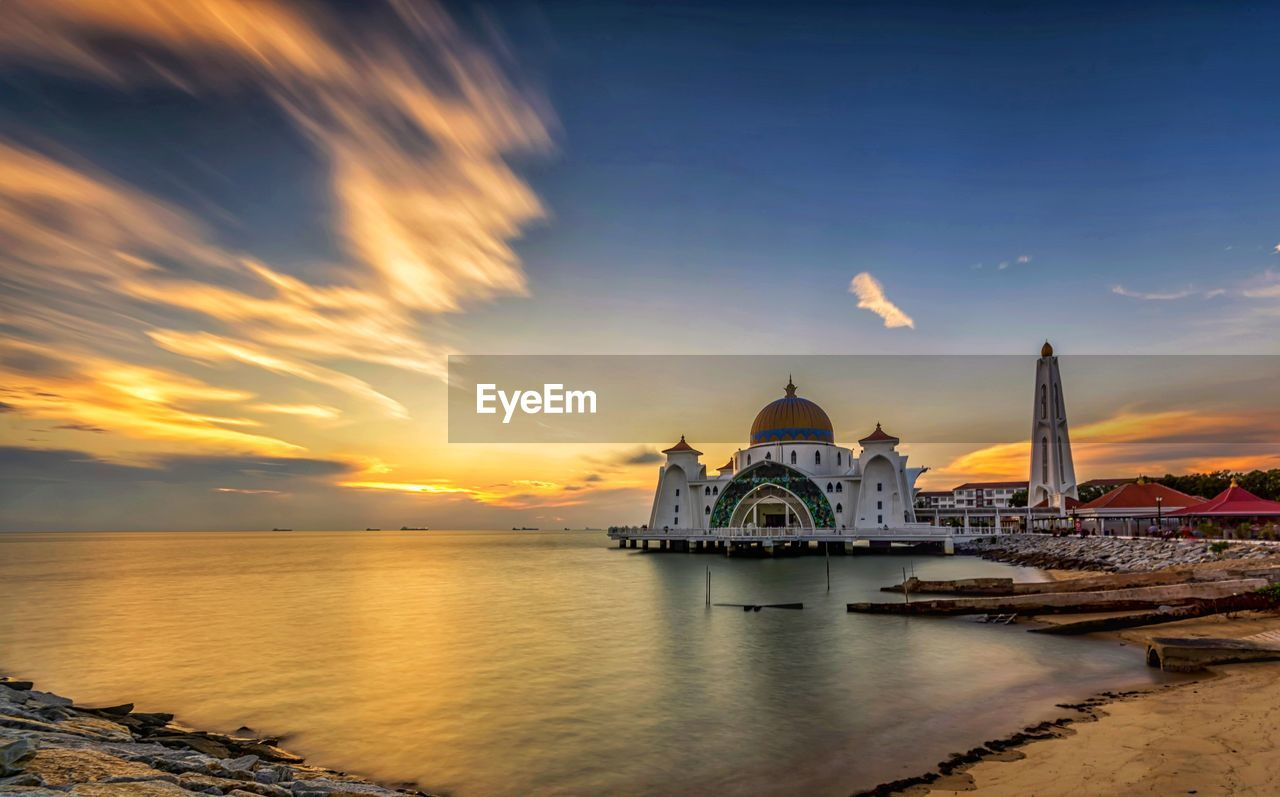 religion, sunset, spirituality, sky, place of worship, architecture, built structure, cloud - sky, building exterior, travel destinations, water, sea, dome, tourism, outdoors, no people, nature, scenics, beauty in nature, day