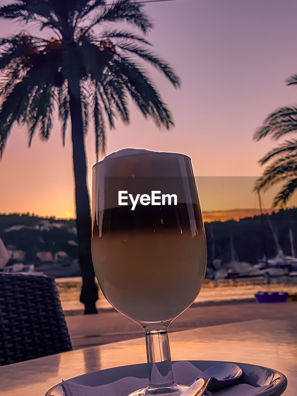 drink, alcohol, glass, sunset, refreshment, palm tree, wine, food and drink, wineglass, tropical climate, sky, tree, table, nature, plant, no people, drinking glass, household equipment, focus on foreground, orange color, red wine