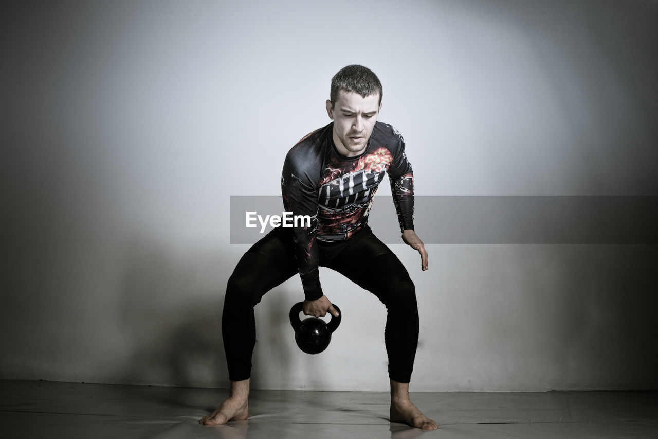 Young Man Lifting Kettle At Gym