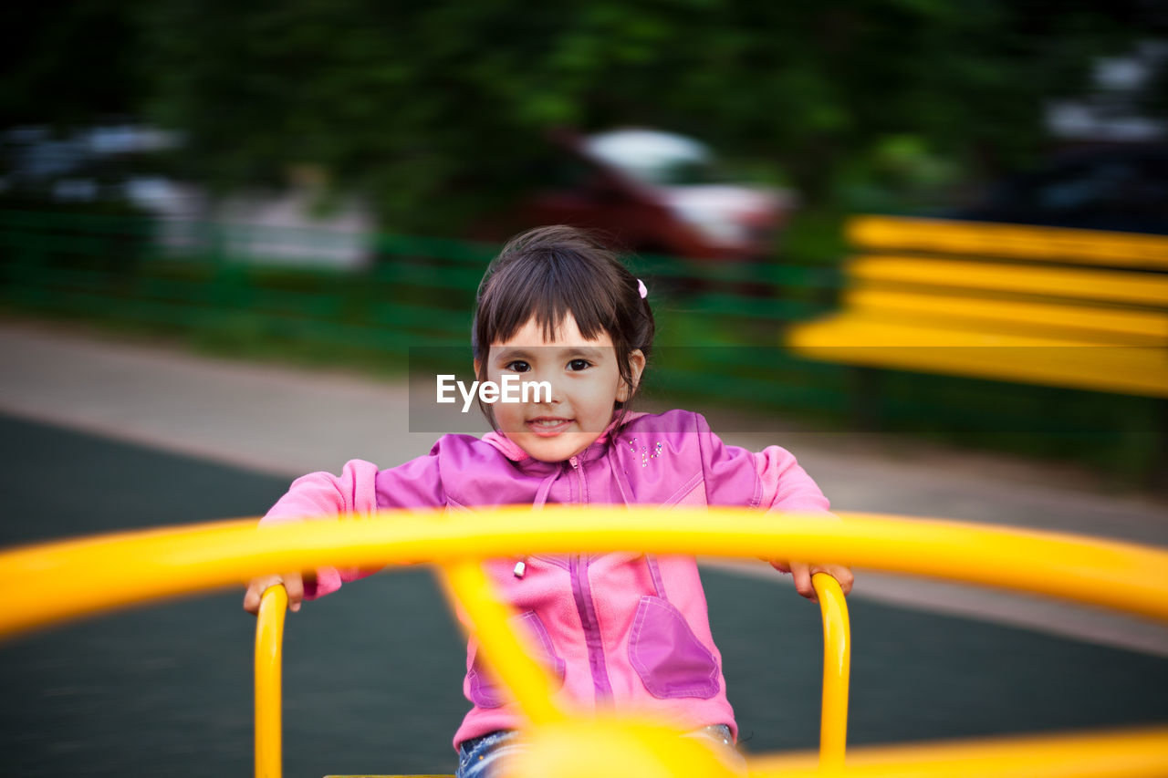 Portrait of cute girl playing on outdoor play equipment in playground