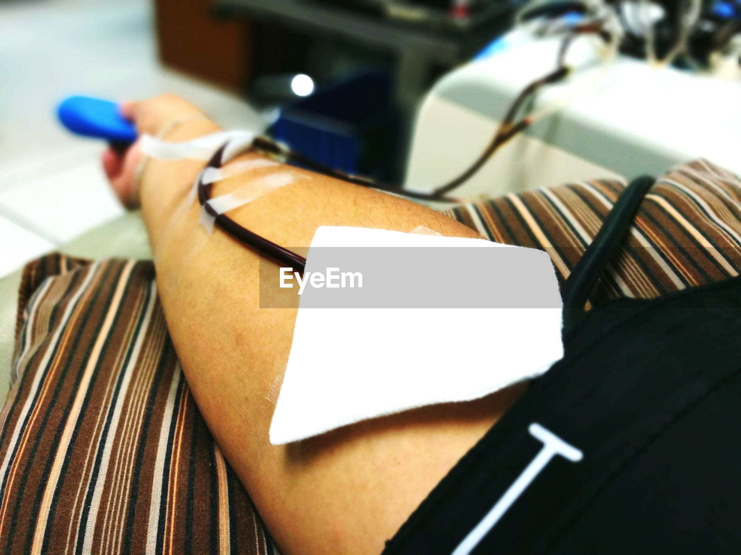 Cropped hand of man with iv drip on bed at hospital