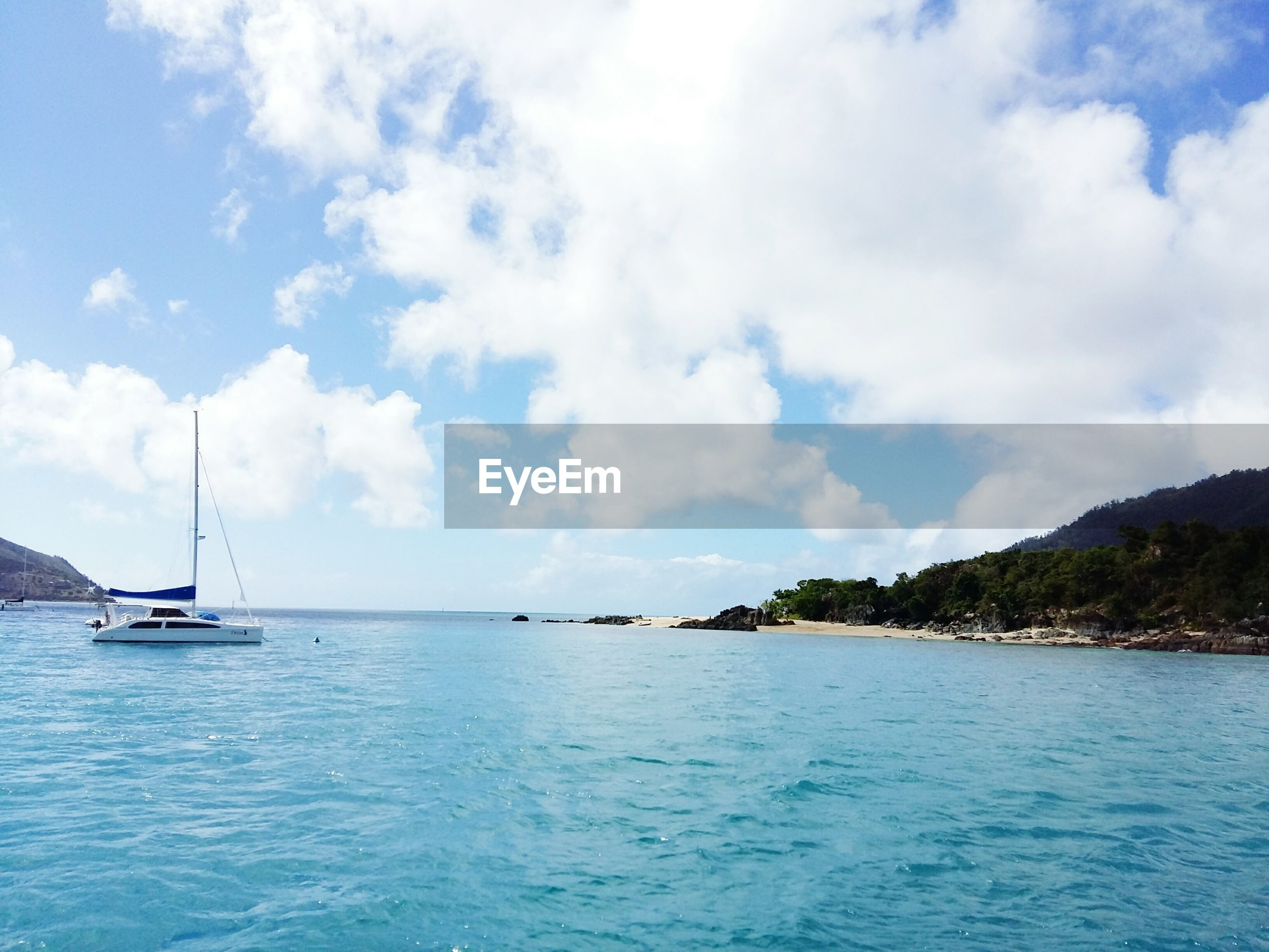 water, nautical vessel, sea, sky, boat, mode of transport, tranquil scene, tranquility, scenics, cloud - sky, beauty in nature, rippled, nature, cloud, blue, sailboat, sailing, day, mountain, cloudy, idyllic, outdoors, no people, mast, calm, non-urban scene, seascape, remote, ocean, non urban scene