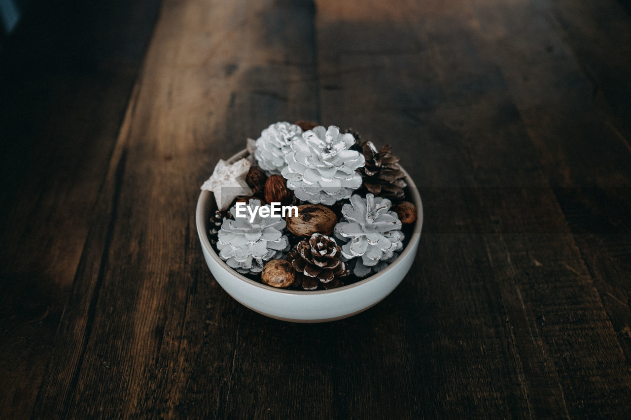 High Angle View Of Pine Cones And Walnuts In Bowl On Table During Christmas