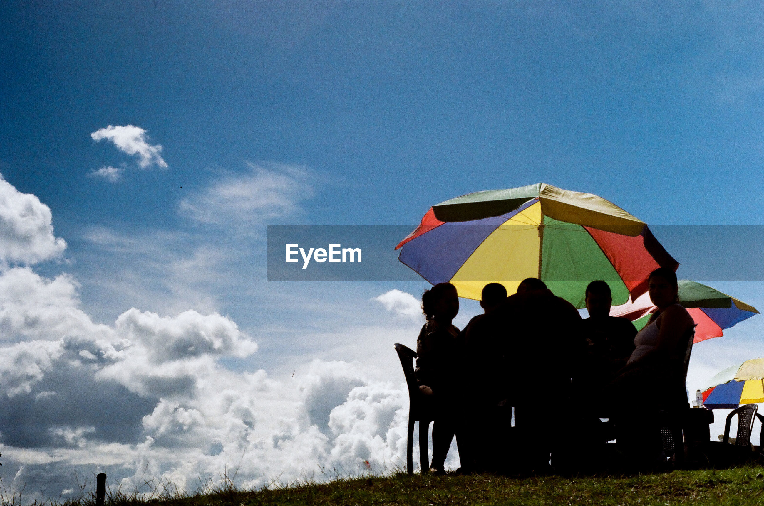 Low angle view of friends sitting at table on field against sky