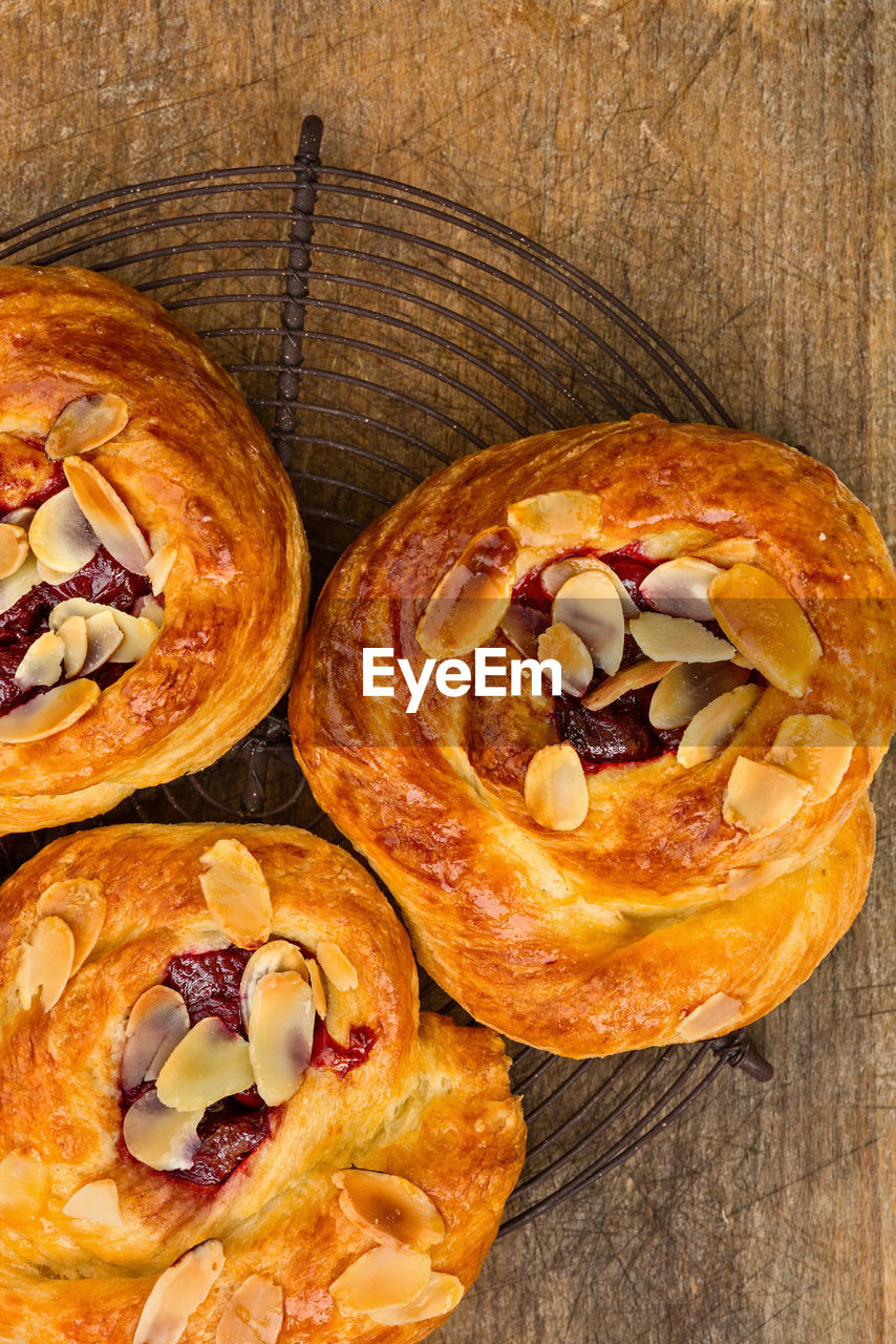 food and drink, food, freshness, baked, sweet food, still life, table, high angle view, wood - material, indoors, close-up, no people, directly above, unhealthy eating, indulgence, dessert, ready-to-eat, sweet, bread, snack, temptation, french food, muffin, puff pastry