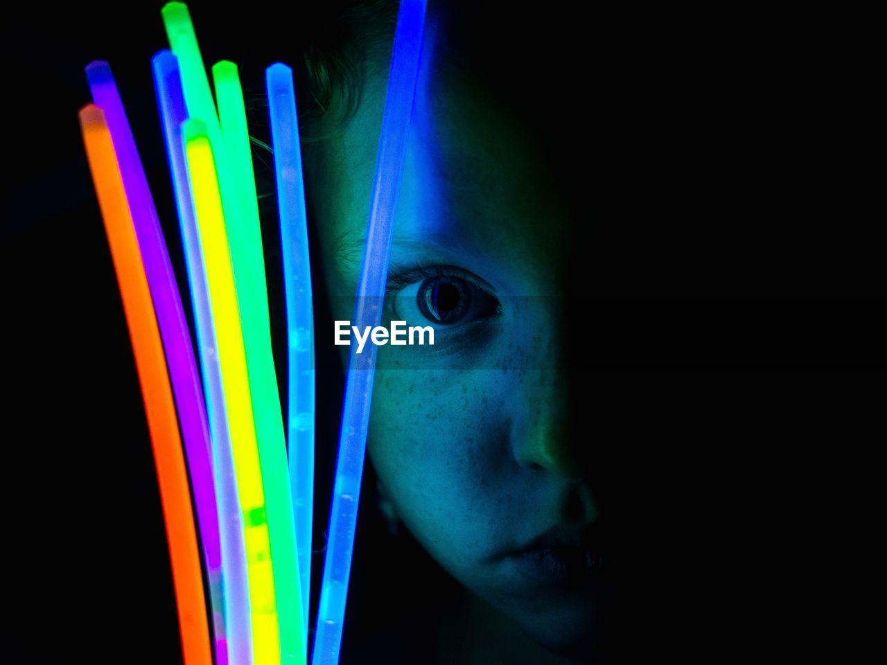 Portrait Of Girl Holding Glow Sticks Against Black Background