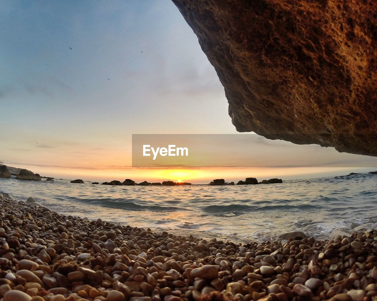 Surface Level View Of Pebbles At Beach During Sunset