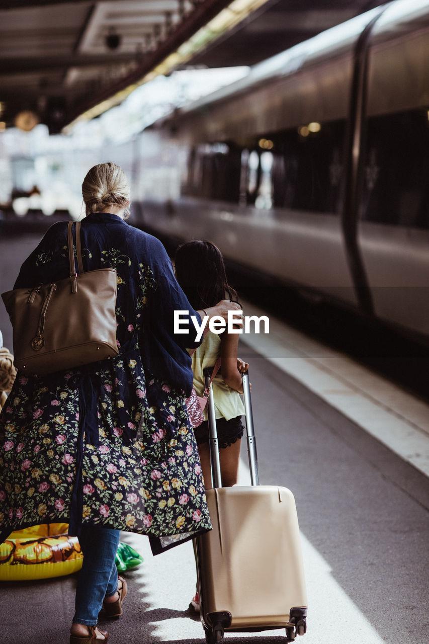 REAR VIEW OF WOMEN WALKING ON RAILROAD STATION