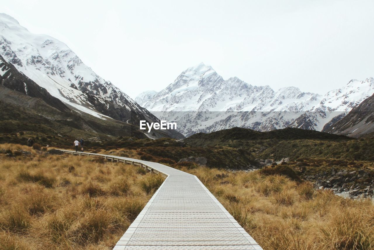 Boardwalk Against Snowcapped Mountains