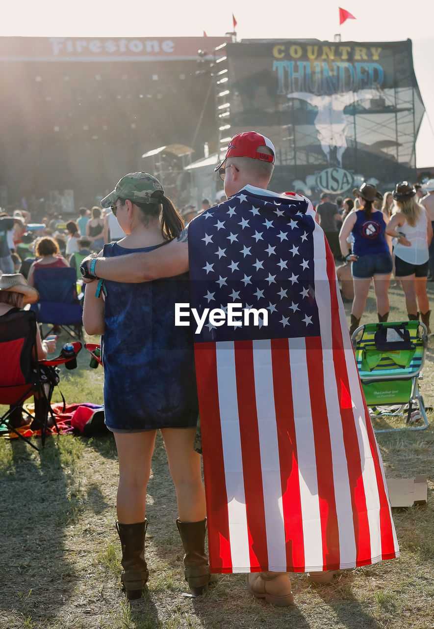 flag, striped, real people, patriotism, rear view, built structure, togetherness, outdoors, standing, men, celebration, building exterior, day, architecture, full length, large group of people, women, people